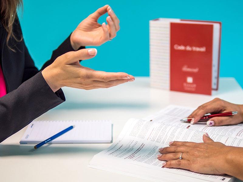 Une avocate et une cliente échangent sur un bureau devant un code du travail